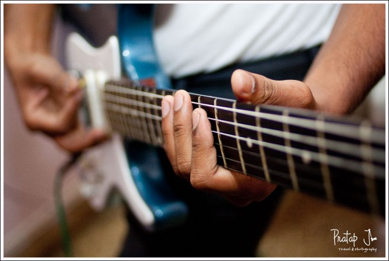 A photo of a man playing a guitar