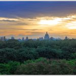 A view of sunset behind Vidhan Soudha in Bangalore with green trees in the foreground