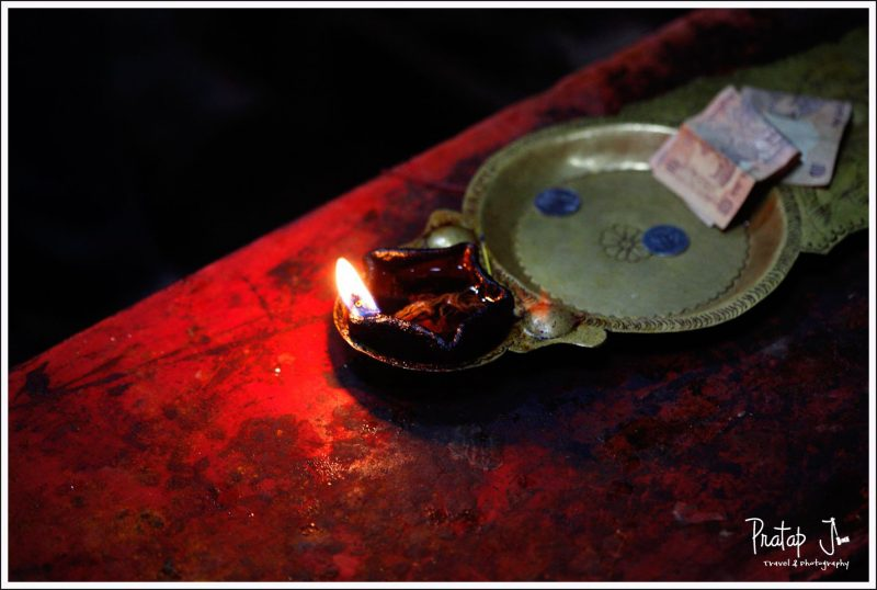 A photo of the flame in an aarthi inside a temple